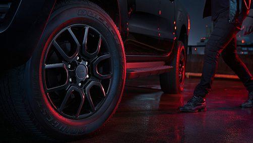 Visão das rodas da Ford Ranger Black. Também é possível ver as pernas de alguém se aproximando.